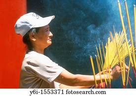 Vietnam, Ho Chi Minh City, A woman waving incense sticks during