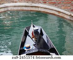 af7a656e212 Gondola passing under a bridge with the Venetian flag and straw hat of the  gondolier
