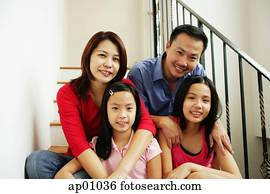 Family of four sitting on stairs, looking at camera, family portrait