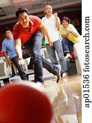 Man bowling, friends in the background, cheering