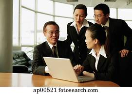 Executives in office, having a meeting, laptop open in front of them