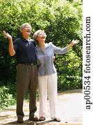 Senior couple looking up, hands outstretched