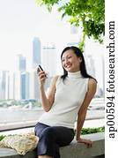 Young woman, looking at mobile phone, smiling