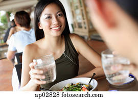 Couple having a meal in restaurant, holding glasses of water
