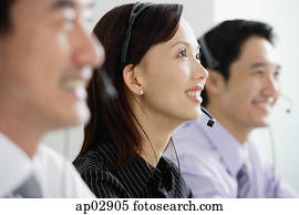 Executives in a row, wearing headsets, looking away