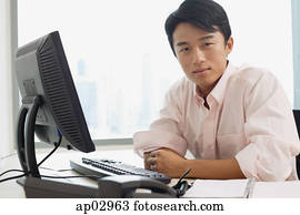 Male executive sitting at office desk, looking at camera
