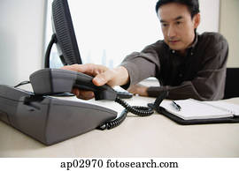 Male executive sitting at office desk, reaching for telephone