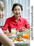Senior adult at dining table, smiling at camera, granddaughter in the foreground