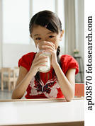Girl sitting at table, drinking glass of milk