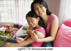 Mother hugging daughter, both looking at camera