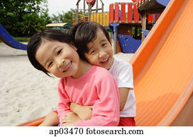 Two young girls sitting on slide, embracing, smiling at camera