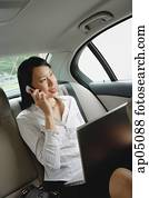 Businesswoman in car using laptop and mobile phone