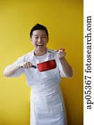 Man wearing apron and holding saucepan