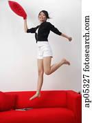 Young woman jumping on sofa, smiling at camera