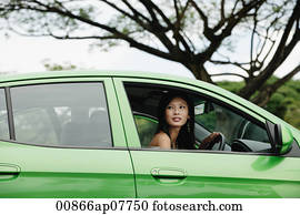 A young woman drives a green car