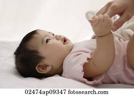 baby girl holding woman's hand