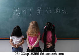 three young girls looking at Chinese characters