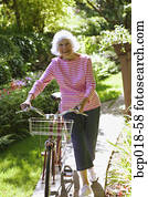 A senior woman walking her bicycle.