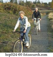 Senior couple riding bikes on a trail