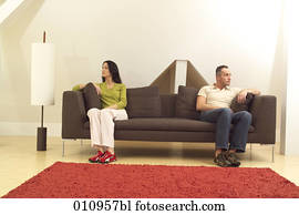 Couple sitting on sofa looking in different directions
