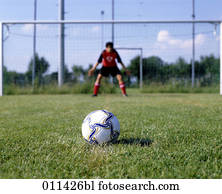 football lying on penalty spot with goalkeeper in background