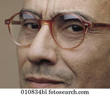 Mature man with horn-rimmed glasses looking into the camera