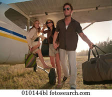one man and two women posing like fashion models near small propeller plane