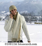 portrait of young man in winter clothes with cellular phone