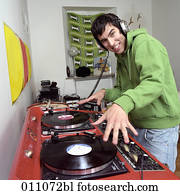 Teenage boy with headphones using professional record player