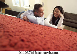 Young couple lying on the carpet of their living room looking at each other