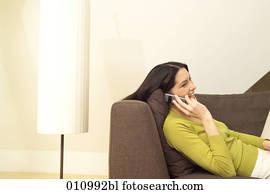 Young woman talking on mobile phone while lying on the sofa