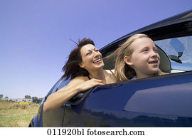 happy mother and daughter sitting in car together
