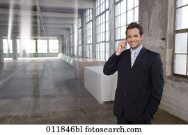 portrait of smiling businessman making a phone call in factory building