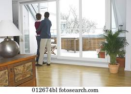 mature couple looking out of the window of their living room