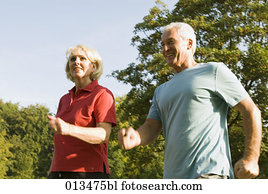 close-up of mature couple running through park