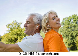 close-up of mature man and woman back to back listening to music