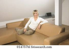 full body portrait of smiling young woman sitting on leather couch in living room