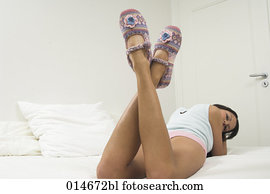 rear view of young woman relaxing on bed showing her slippers