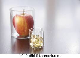 still life of apple and pills in jars