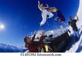 two young women in bikini tops jumping from roof of alpine hut in winter
