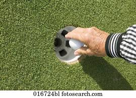 close-up of mature adult taking golf ball from hole