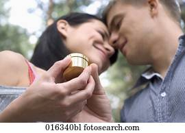 young couple looking at each other woman receiving present in golden box