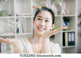 portrait of young japanese girl playing with soap bubbles