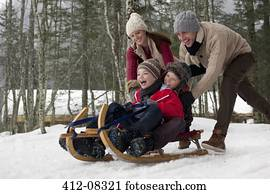 Happy family sledding in snowy woods