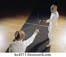 1960s two men fencing protective suits mask swords epees Stock