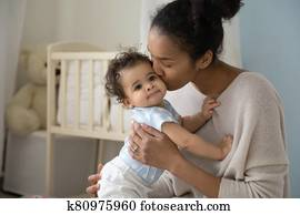 Loving biracial mom hug and kiss little baby
