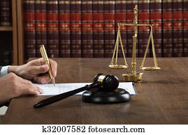 Judge Writing On Legal Documents At Desk