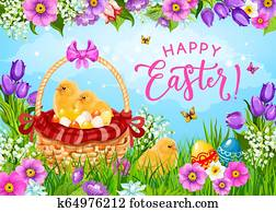 Easter eggs, chicks and flowers in basket