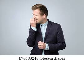Caucasian young man in suit biting nails feeling nervous.
