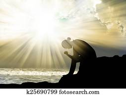 Woman praying to god at sunset